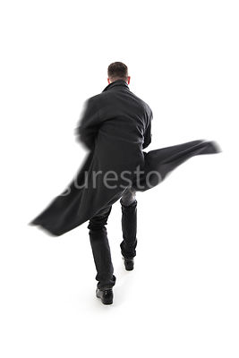 A Figurestock image of a mystery man in a long black coat, running away or fighting – shot from eye level.