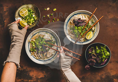 Womans hands with chopsticks and lime over vietnamese soup Pho-Ga