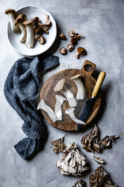 Trumpet and maitake mushrooms on a wooden cutting board.