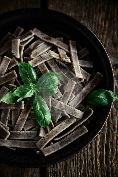 BUCKWHEAT PASTA WITH BASIL ON A WOODEN TABLE