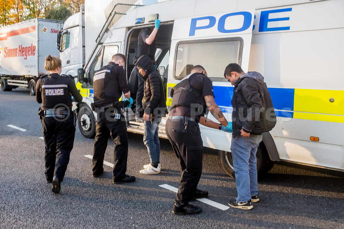 Illegal immigrants being searched and handcuffed by police officers after hiding in a truck just arrived from France