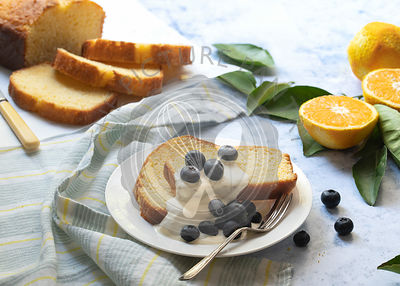 Slices of orange cake with fresh blueberries and cream.