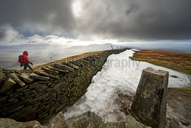 A hiker walking past the summit of Whernside, part of the Three