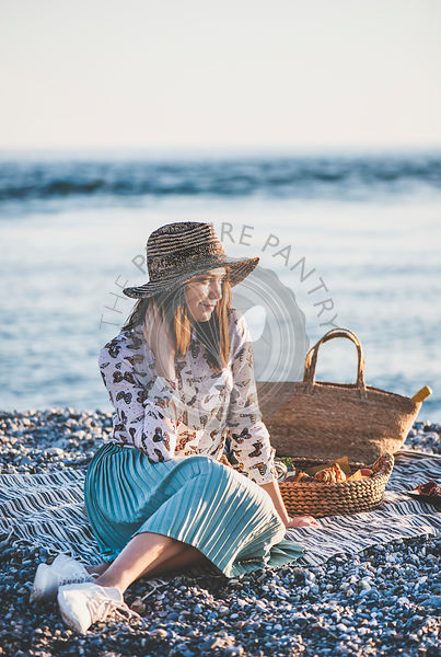 Young woman having picnic at sunset at seaside