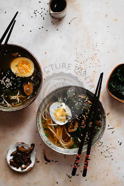 Bowls of miso soup on a light brown surface