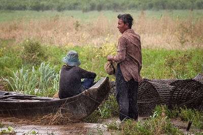 Man and woman are waiting for the rains to pass and start their fishing activities on Tonle Sap, the largest freshwater lake ...