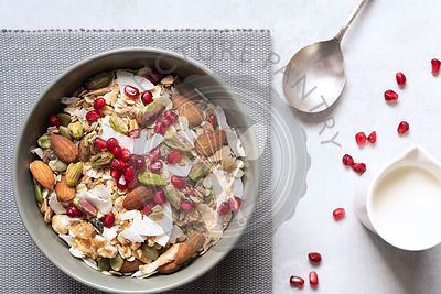 Healthy breakfast bowl of dried fruit, nuts, muesli and pomegranate seeds.