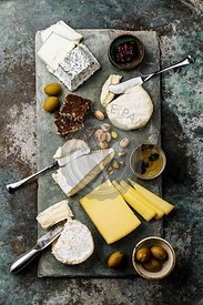 Cheese Plate with different types of cheese Snack assortment on slate serving board