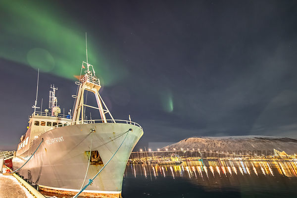 The northern lights above the Polarfront ship, the Tromsø Bridge and the Arctic Cathedral, Norway