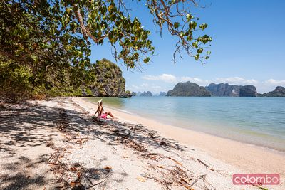 Woman with sarong sitting on beach, Phang Nga bay, Thailand