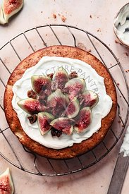 Fig and apple sponge cake on a grey pink surface, decorated with fig slices