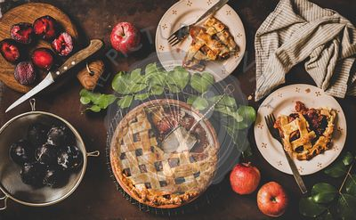 Flat-lay of apple and plum pie and tea setting