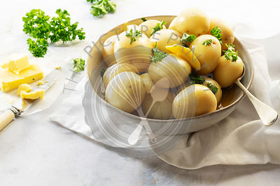 Whole steamed potatoes with butter and parsley in a ceramic bowl.