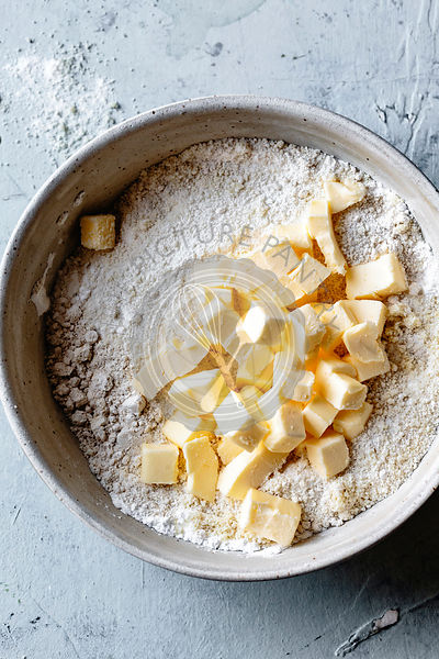 Cold butter cubes with almond flour in a bowl.