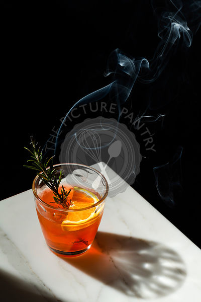 Negroni cocktail with a slice of orange and a smoking rosemary sprig garnish. The view features the corner of a marble tablet...