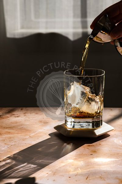 Whiskey being poured into a rocks glass in hard light.