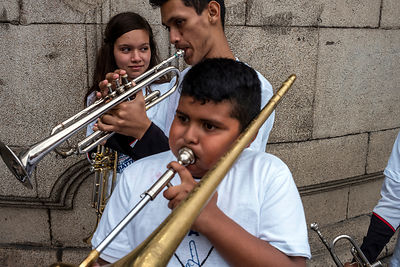 Young musicians tune their instruments before playing at a political rally