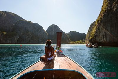Woman on boat prow looking at Maya bay, Phi Phi island, Thailand