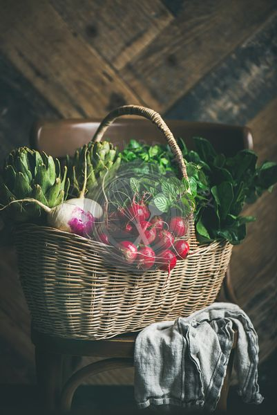 Basket full of of fresh ripe organic vegetables and greens