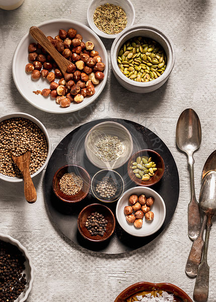 Assortment of spices, seeds and nuts in bowls on gray background