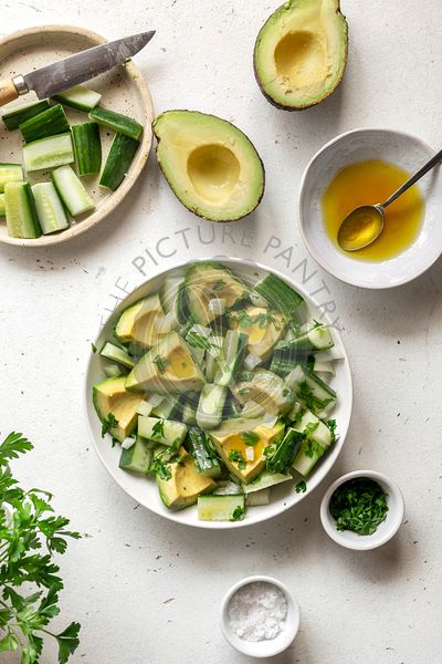 Avocado and cucumber salad in a bowl over white background