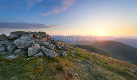 A bright sunset sky over the mountains of the Lake District from the summit og Ramspgill Head with views of The Knott and Res...