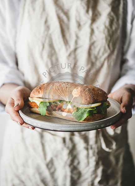 Woman in linen apron holding breakfast sandwich with fried fish