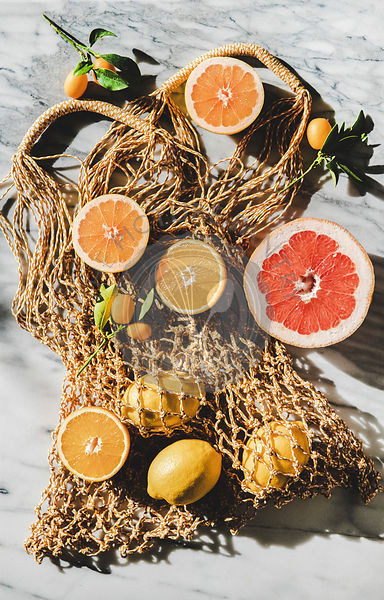 Flat-lay of summer net bag with fresh ripe citrus fruits