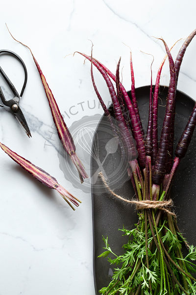 A bunch of washed purple carrots tied with jute twine on an oblong charcoal platter. The surface is a marble tile a halved ca...