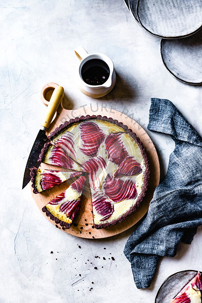 Red wine poached pear custard tart on a wooden serving board.