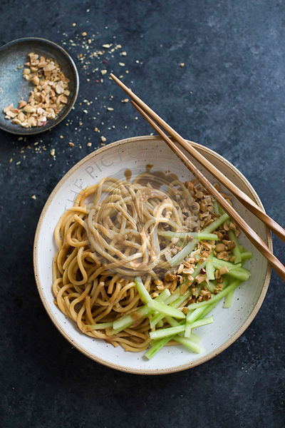 Udon noodles with peanut sauce and cucumber sticks in a bowl with chopsticks.