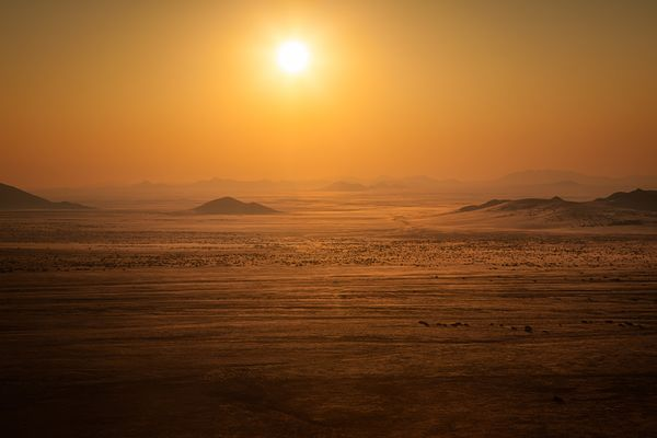 Sun shining low over the Namib desert in late afternoon, turning the landscape into bright orange at the viewpoint called God...