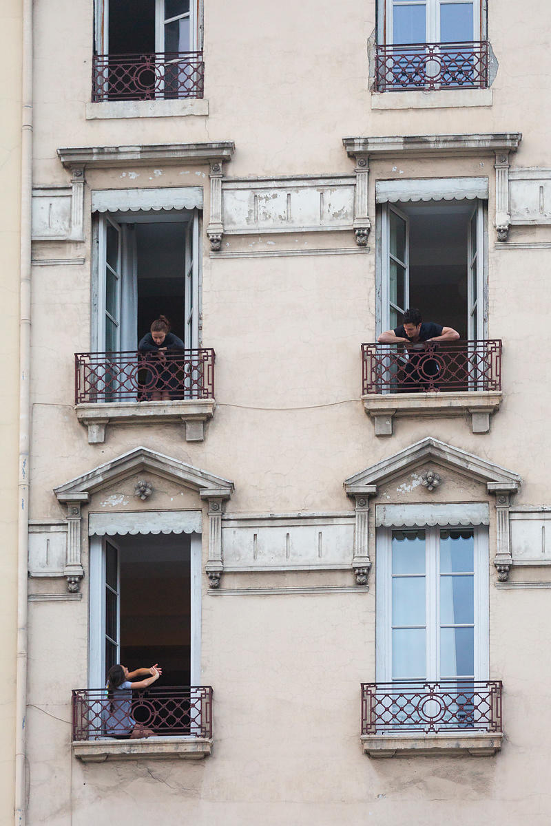 Voisins discutant à leur fenêtre à 20h lors du confinement, rue Leynaud, Lyon, France / Neighbors chatting at their window at...
