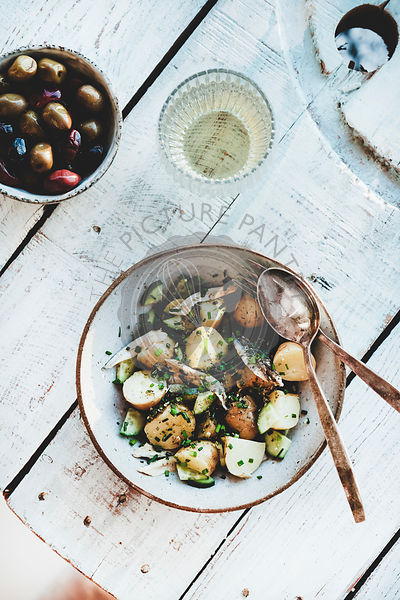 Healthy summer lunch with potato salad, olives and white wine