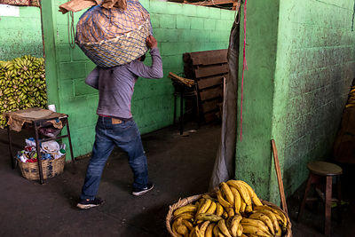 A porter carries bananas through the fruit market