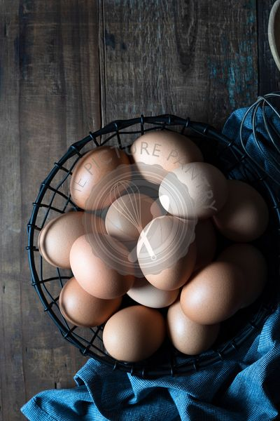 Eggs in a wire basket on a wooden background.