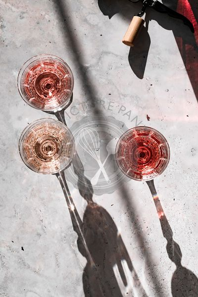 Three shades of Rosé wine in glasses casting hard shadows surrounded by colorful shadows cast from the wine bottles.
