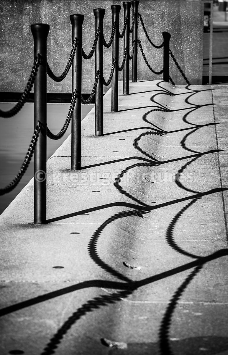 Chain Shadows on Paved Walkway in Black & White