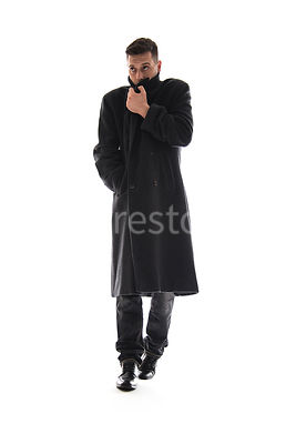 A Figurestock image of a mystery man, turning up the collar of a long black winter coat, walking towards camera – shot from l...
