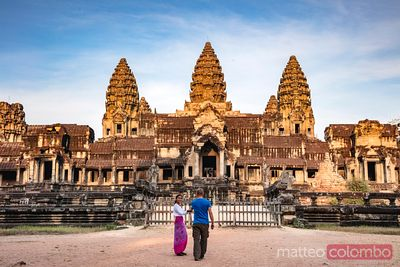 Tourist couple discovering the temple ruins of Angkor, Siem Reap, Cambodia