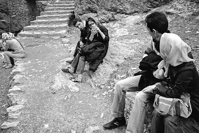 A girl takes a picture of an other couple with her mobile phone on the promonade at Darband.