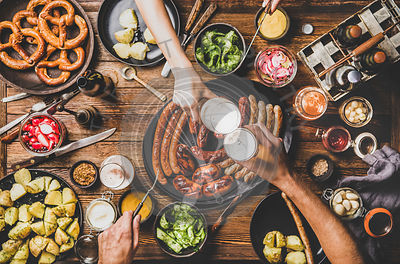 Flat-lay of dinner table with beer, Bavarian sausages and snacks