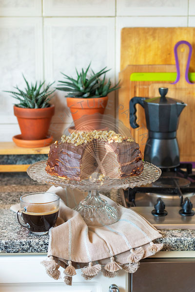 Chocolate crepe cake on a cake stand in the kitchen