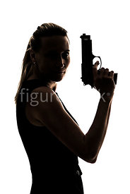 Silhouette of a woman standing with a gun – shot from eye level.