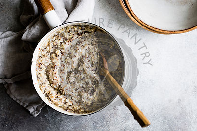 Multigrain porridge in a saucepan with wooden spoon