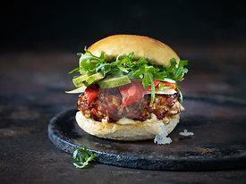 A Spanish burger with salad on a dark background