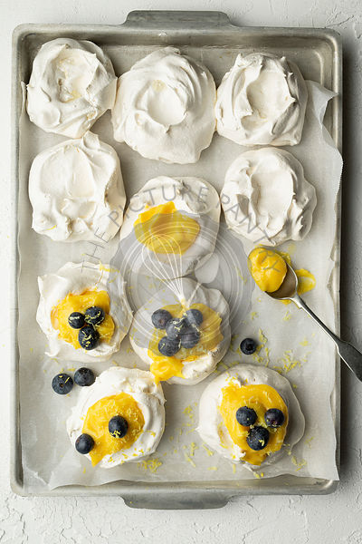 Meringues with lemon curd and blueberries on a baking tray with parchment, on a white textured background. A spoon of lemon c...