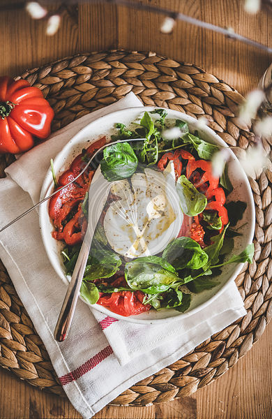 Italian salad with Buratta cheese in white bowl on table