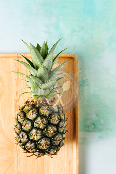 Overhead shot of small pineapple on a wood tray over a blue/green tabletop.