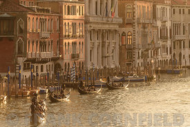 VENICE, ITALY - OCTOBER 25, 2017: Gondolas on the Grand Canal in golden hour sunlight.